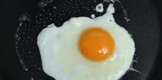 A wife was making a breakfast of fried eggs for her husband.